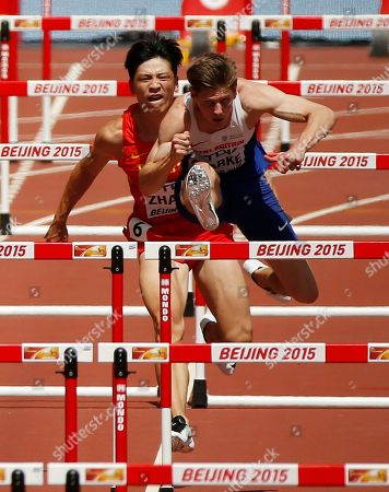 Stock Image of China's Zhang Honglin, left, crosses into the lane of Britain's Lawrence Clarke before getting injured in a men's 110m hurdles round one heat at the World Athletics Championships at the Bird's Nest stadium in Beijing