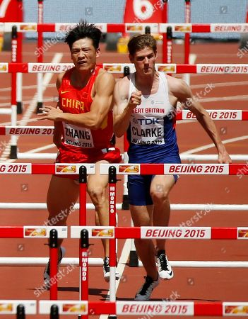 China's Zhang Honglin, left, crosses into the lane of Britain's Lawrence Clarke before getting injured in a men's 110m hurdles round one heat at the World Athletics Championships at the Bird's Nest stadium in Beijing