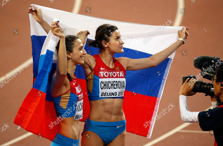 Gold medalist Maria Kuchina, left, and bronze medalist Anna Chicherova, both from Russia, celebrate at the end of the women's high jump final at the World Athletics Championships at the Bird's Nest stadium in Beijing
