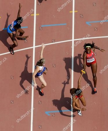 Jessica Beard, right, of the United States hands-off the baton to Sanya Richards-Ross as other competitors in a women's 4x400m relay round one heat reach out to make baton changeovers at the World Athletics Championships at the Bird's Nest stadium in Beijing