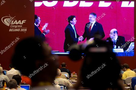 Journalists watch a screen at a media center showing a live feed of newly elected International Association of Athletics Federations President Sebastian Coe, center left, is congratulated by Sergei Bubka after the election results were announced at the IAAF Congress at National Convention Center in Beijing . The 58-year-old Coe has won a four-year term as president of the governing body for track and field, beating Bubka in an election Wednesday and given the mandate to restore the image of the IAAF amid a doping controversy