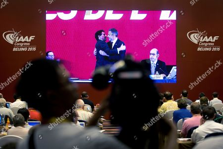 A cameraman films as journalists watch a screen at a media center showing a live feed of newly elected International Association of Athletics Federations President Sebastian Coe, center left, being congratulated by Sergei Bubka after the election results were announced at the IAAF Congress at National Convention Center in Beijing . The 58-year-old Coe has won a four-year term as president of the governing body for track and field, beating Bubka in an election Wednesday and given the mandate to restore the image of the IAAF amid a doping controversy