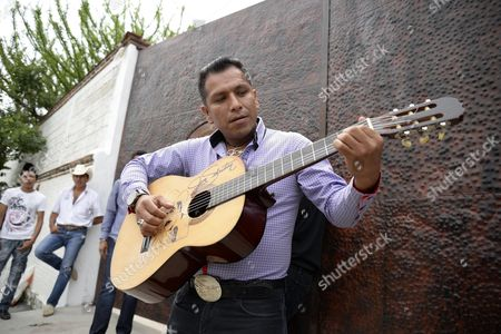"""CORRECTS THE NUMBER OF GRAMMYS AWARDED TO SEBASTIAN - Domingo David, a fan of Mexican ballad singer Joan Sebastian, plays the guitar outside of Sebastian's home in Teacalco, Mexico, . Sebastian, one of Mexico's great ballad singers, died on July 13 at age 64. He was best known for sentimental love songs like """"Tatuajes"""" and """"Secreto de Amor,"""" sometimes set to simple guitar arrangements and sometimes sung on horseback. Sebastian won four Grammy awards and seven Latin Grammy prizes during his career"""