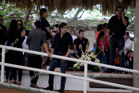 """Julian Figueroa CORRECTS THE NUMBER OF GRAMMYS AWARDED TO SEBASTIAN - Julian Figueroa, son of Mexican ballad singer Joan Sebastian, stands amongst guests during his father's wake at their home in Teacalco, Mexico, . Sebastian, one of Mexico's great ballad singers, died on July 13 at age 64. He was best known for sentimental love songs like """"Tatuajes"""" and """"Secreto de Amor,"""" sometimes set to simple guitar arrangements and sometimes sung on horseback. Sebastian won four Grammy awards and seven Latin Grammy prizes during his career"""