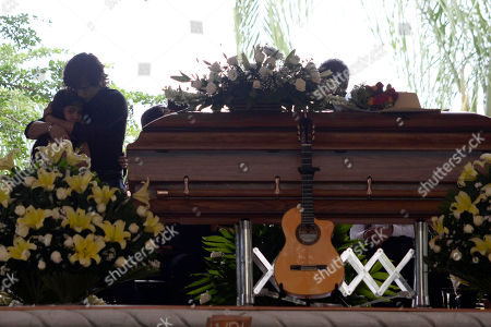 """CORRECTS THE NUMBER OF GRAMMYS AWARDED TO SEBASTIAN - Julian Figueroa, second left, embraces another unidentified family member during the wake for his father, Mexican ballad singer Joan Sebastian at his home in Teacalco, Mexico, . Sebastian, one of Mexico's great ballad singers, died on July 13 at age 64. He was best known for sentimental love songs like """"Tatuajes"""" and """"Secreto de Amor,"""" sometimes set to simple guitar arrangements and sometimes sung on horseback. Sebastian won four Grammy awards and seven Latin Grammy prizes during his career"""