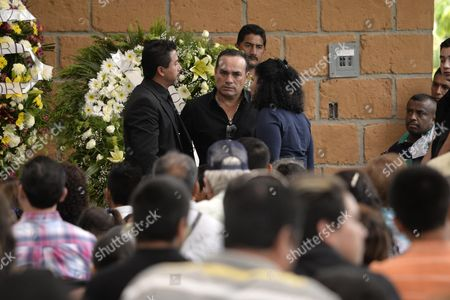 """Federico Figeroa CORRECTS THE NUMBER OF GRAMMYS AWARDED TO SEBASTIAN - People stand next to Federico Figueroa, center, during the wake for his brother, Mexican ballad singer Joan Sebastian at his home in Teacalco, Mexico, . Sebastian, one of Mexico's great ballad singers, died on July 13 at age 64. He was best known for sentimental love songs like """"Tatuajes"""" and """"Secreto de Amor,"""" sometimes set to simple guitar arrangements and sometimes sung on horseback. Sebastian won four Grammy awards and seven Latin Grammy prizes during his career"""