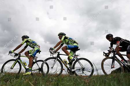 Spain's Alberto Contador, center, follows teammate Italy's Ivan Basso, left, during the eighth stage of the Tour de France cycling race over 181.5 kilometers (112.8 miles) with start in Rennes and finish in Mur-de-Bretagne, France