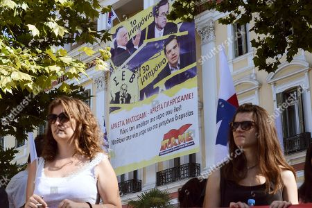 Members of the Communist-affiliated PAME labor union gather next to an anti-austerity banner depicting and reading ''1st memorandum with former Greek Prime Minister George Papandreou, 2nd memorandum with former Prime Minister Antonis Samaras, 3rd memorandum with Greek Prime Minister Alexis Tsipras. We bled enough, we paid enough'' during a protest at the Ministry of Macedonia and Thrace in the northern Greek port city of Thessaloniki, . Talks on a bailout worth 85 billion euros ($94 billion) will start if Parliament agrees by Wednesday to creditors' demands, including painful tax hikes and pension cuts