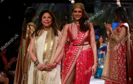 Bollywood actress Aditi Rao Hydari, right, walks along with Indian designer Ritu Kumar during the Lakme Fashion Week in Mumbai, India