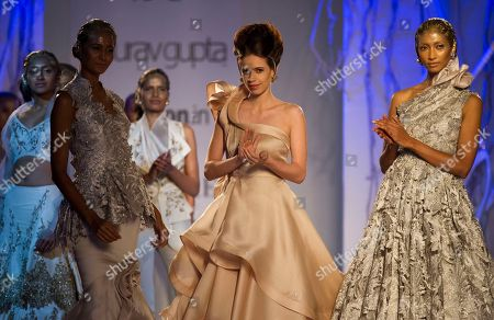 An Indian bollywood actor Kalki Koechlin, center, displays a creation by Indian designer Gaurav Gupta at the Amazon India Couture Week 2015 in New Delhi, India