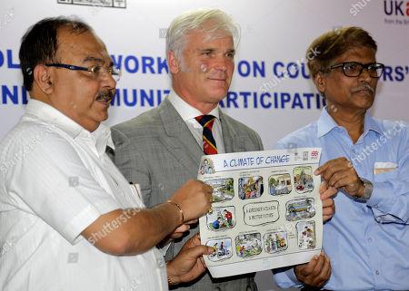 U.K. International Development Minister Desmond Swayne, flanked by Kolkata Mayor Sovan Chatterjee, left and West Bengal state Environment Minister Sudarshan Ghosh Dastidar release an awareness poster on climate change in Kolkata, India