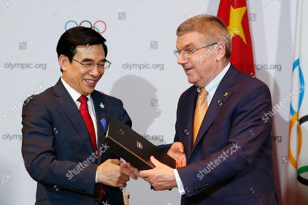 Stock Image of Wang Anshun, Thomas Bach Beijing Mayor and President of the Beijing 2022 Olympic Winter Games Wang Anshun, left, exchanges the document with International Olympic Committee President Thomas Bach at the signing ceremony after Beijing was selected to host the 2022 Olympic Winter Games at the IOC meeting in Kuala Lumpur, Malaysia, . Beijing was selected Friday to host the 2022 Winter Olympics, becoming the first city awarded both the winter and summer games