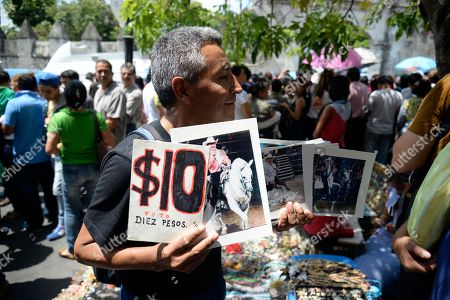 """A man sells photos of Mexican ballad singer Joan Sebastian outside the cathedral in Cuernavaca, Mexico, . The Grammy and Latin Grammy award winner died Monday. He was best known for sentimental love songs such as, """"Tatuajes"""" and """"Secreto de Amor."""" He was 64"""