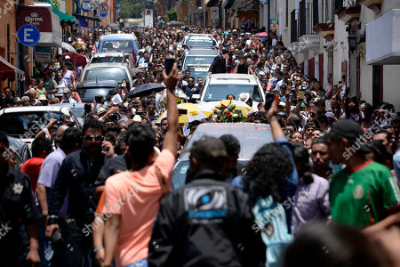 """Thousands take part in the funeral procession of Mexican ballad singer Joan Sebastian, as it makes its way through the streets of Cuernavaca, Mexico, . The Grammy and Latin Grammy award winner died Monday. He was best known for sentimental love songs such as, """"Tatuajes"""" and """"Secreto de Amor."""" He was 64"""