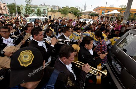 """Mariachis accompany the hearse transporting the coffin containing the remains of Mexican ballad singer Joan Sebastian at the Plaza Garibaldi in Mexico City, . The Grammy and Latin Grammy award winner died Monday. He was best known for sentimental love songs such as, """"Tatuajes"""" and """"Secreto de Amor."""" He was 64"""