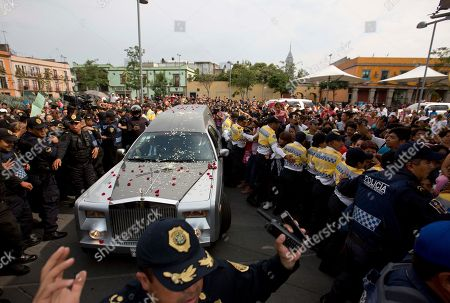 """A hearse transporting the coffin containing the remains of Mexican ballad singer Joan Sebastian drives through the Plaza Garibaldi during a funeral procession in Mexico City, . The Grammy and Latin Grammy award winner died Monday. He was best known for sentimental love songs such as, """"Tatuajes"""" and """"Secreto de Amor."""" He was 64"""