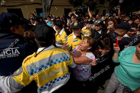"""Transportation police prevent fans from touching the hearse transporting the coffin containing the remains of Mexican ballad singer Joan Sebastian, as the hearse drives through Plaza Garibaldi in a funeral procession in Mexico City, . The Grammy and Latin Grammy award winner died Monday. He was best known for sentimental love songs such as, """"Tatuajes"""" and """"Secreto de Amor."""" He was 64"""