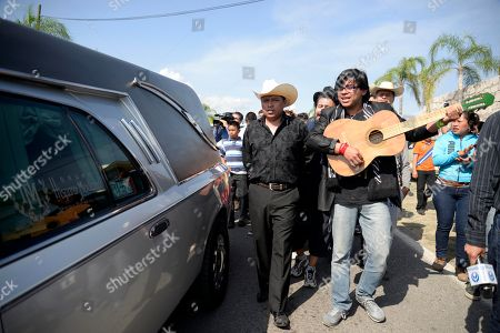 """Musicians accompany the hearse transporting the coffin containing the remains of Mexican ballad singer Joan Sebastian in Teacalco, Mexico, . The Grammy and Latin Grammy award winner died Monday. He was best known for sentimental love songs such as, """"Tatuajes"""" and """"Secreto de Amor."""" He was 64"""