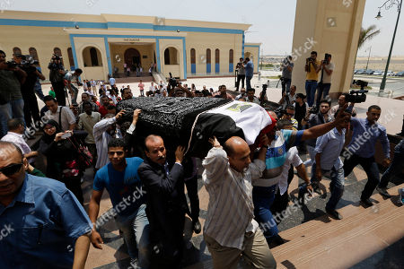 """Mourners carry the coffin of Egyptian actor Omar Sharif for a funeral procession at the Hussein Tantawi Mosque in Cairo, Egypt, . Sharif, the Egyptian-born actor with the dark, soulful eyes who soared to international stardom in movie epics, """"Lawrence of Arabia"""" and """"Doctor Zhivago,"""" died in a Cairo hospital of a heart attack, on Friday, July 10. He was 83"""