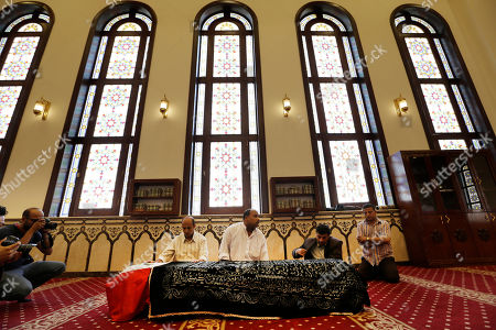 """Mourners pray next to the coffin of Egyptian actor Omar Sharif during his funeral procession at the Hussein Tantawi Mosque in Cairo, Egypt, . Sharif, the Egyptian-born actor with the dark, soulful eyes who soared to international stardom in movie epics, """"Lawrence of Arabia"""" and """"Doctor Zhivago,"""" died in a Cairo hospital of a heart attack, on Friday, July 10. He was 83"""