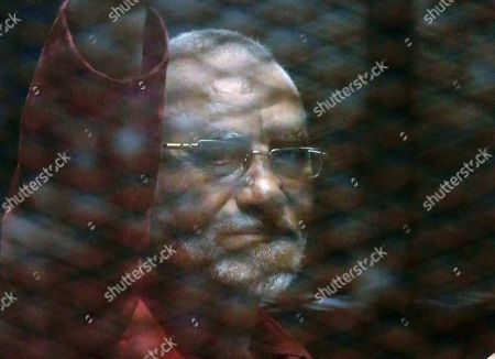 Mohammed Badie Muslim Brotherhood spiritual leader, Mohammed Badie wearing a red jumpsuit that designates he has been sentenced to death, waves from a defendants cage in a makeshift courtroom at the Torah prison, southern Cairo, Egypt