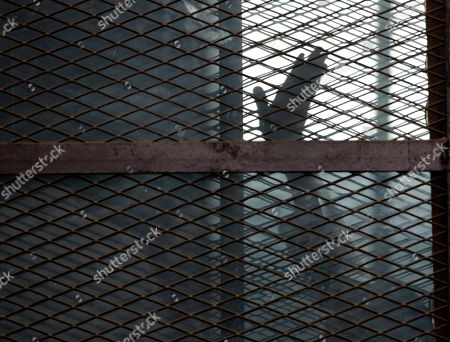 A Muslim Brotherhood member gestures from a defendants cage in a courtroom in Torah prison, southern Cairo, Egypt, . The court sentenced Muslim Brotherhood spiritual leader, Mohammed Badie and other Brotherhood members to life in prison on over an attack on a police station in 2013