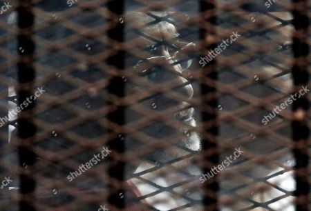 Muslim Brotherhood spiritual leader, Mohammed Badie wearing a red jumpsuit that designates he has been sentenced to death, listens to his verdict from a defendants cage in a makeshift courtroom at the Torah prison, southern Cairo, Egypt, . The court sentenced Badie and other Brotherhood members to life in prison on over an attack on a police station in 2013