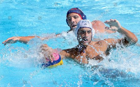 Kyriakos Pontikeas of Greece, front, and Tony Azevedo of the USA, rear, challenge for the ball during the men's water polo preliminary round group B match between Greece and the USA at the Swimming World Championships in Kazan, Russia, . Greece defeated the USA by 11-10