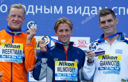 United States' gold medal winner Jordan Wilimovsky is flanked by Netherlands' silver medal winner Ferry Weertman, left, and Greece's bronze medal winner Spyridon Gianniotis during the ceremony for the men's 10km open water swim competition at the Swimming World Championships in Kazan, Russia