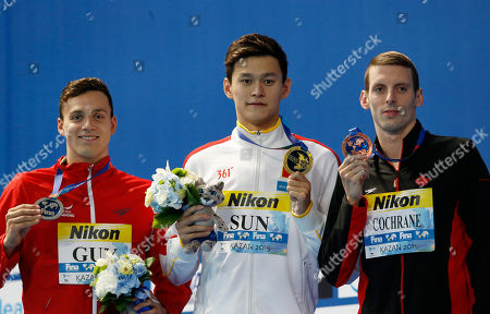 China's gold medal winner Sun Yang is flanked by Britain's silver medal winner James Guy, left, and Canada's bronze medal winner Ryan Cochrane during ceremony for the men's 400m freestyle final at the Swimming World Championships in Kazan, Russia
