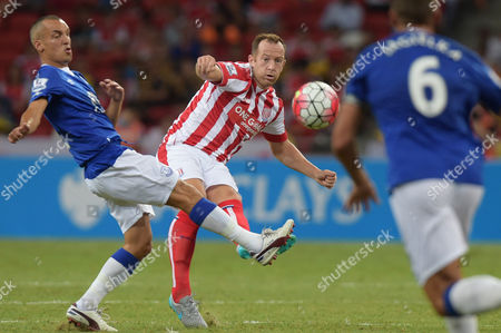 Charlie Adam, Leon Osman Stoke City's Charlie Adam, center, makes a pass over Everton's Leon Osman, left, in their soccer match for the Barclays Asia Trophy in Singapore