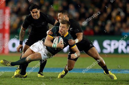 South Africa's Handre Pollard, center, is tackled by New Zealand Lima Sopoaga, right, whilst teammate Liam Messam, left, watches during their Rugby Championship test match at Ellis Park stadium in Johannesburg, South Africa