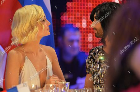 Conchita Wurst, who won the 2014 ESC for Austria, right, talks to Polina Gagarina representing Russia during the final of the Eurovision Song Contest in Austria's capital Vienna