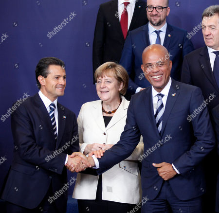 Mexico's President Enrique Pena Nieto, left, shakes hands with Haiti's President Michel Joseph Martelly during a group photo opportunity at the EU-CELAC summit in Brussels on . European leaders and their Latin America and the Caribbean counterparts meet on a biannual basis in an effort to maintain international and economic ties. At center is German Chancellor Angela Merkel
