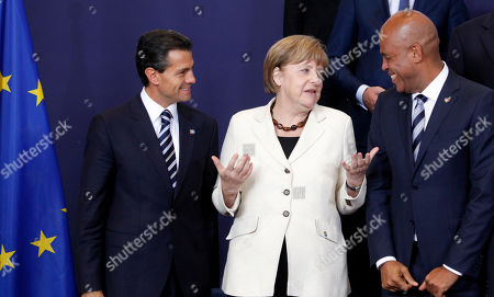 Mexico's President Enrique Pena Nieto, left, speaks to German Chancellor Angela Merkel, center, and Haiti's President Michel Joseph Martelly during a group photo opportunity at the EU-CELAC summit in Brussels on . European leaders and their Latin America and the Caribbean counterparts meet on a biannual basis in an effort to maintain international and economic ties