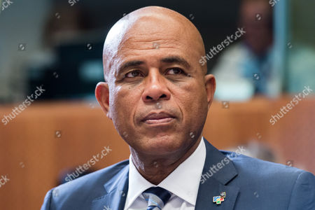 """Haiti's President Michel Joseph Martelly waits for the start of a round table meeting at the EU-CELAC summit in Brussels. Hostile comments made by Martelly to a woman at a campaign rally in Haiti have prompted a party in his coalition to remove three officials from his government. Martelly was at a rally in late July 2015 when a woman complained that his government failed to bring electricity to her community. Haitian media reported that he told her in Haitian Creole to """"go get a man and go in the bushes"""" to have sex"""