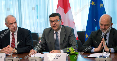 European Commissioner for Economic and Financial Affairs Pierre Moscovici, right, Latvian Finance Minister Janis Reirs, center, and Switzerland's State Secretary for International Finance Jacques de Watteville participate in a signing ceremony regarding taxation between Switzerland and the EU at the EU Council building in Brussels on