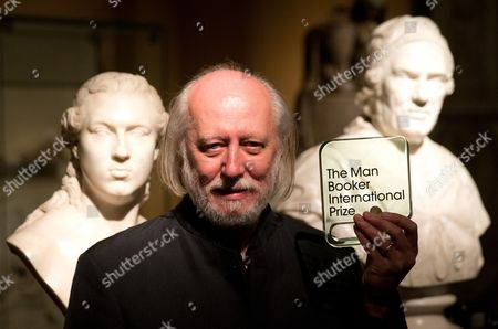 Hungary's Laszlo Krasznahorkai, the winner of the Man Booker International Prize, poses for photographers with the trophy shortly after the award ceremony at the Victoria and Albert Museum in London, . The Man Booker International Prize is awarded every two years to a living author for a body of work published either originally in English or available in translation in the English language