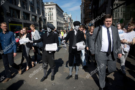 Men dressed as 1920s newspaper boys with 'greyscale' make up pose for photographs as they hand out specially made newspapers that feature two chapters of the latest novel featuring fictional Belgian detective Hercule Poirot outside Oxford Circus underground train station in London, . The promotional event was to celebrate the launch of 'The Monogram Murders' on paperback by contemporary British author Sophie Hannah and to mark 125 years since the birth of Poirot's creator British author Agatha Christie