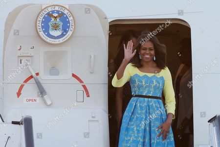 U.S. first lady Michelle Obama waves as she arrives with her daughters Malia and Natasha, and her mother Marian Robinson as she disembarks from a plane at Stansted Airport in Stansted, England, . Michelle Obama is due to meet with female students in London on Tuesday to encourage them to pursue top educational goals
