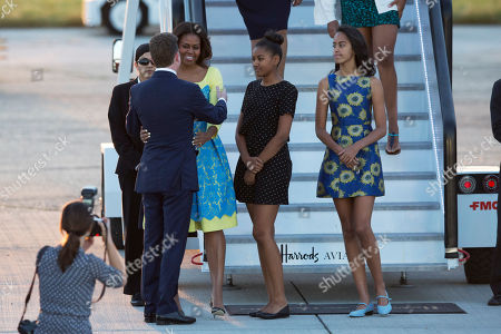 U.S. first lady Michelle Obama, her daughters Malia, right, and Natasha, center, are greeted by U.S, ambassador to the UK Matthew Barzun, left, as they disembark from a plane upon their arrival at Stansted Airport in Stansted, England, . Michelle Obama is due to meet with female students in London on Tuesday to encourage them to pursue top educational goals