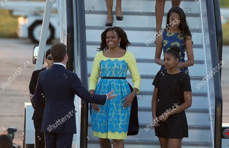Stock Picture of U.S. first lady Michelle Obama, center, her daughters Malia, top right, and Natasha, bottom right, are greeted by U.S, ambassador to the UK Matthew Barzun, left, as they disembark from a plane upon their arrival at Stansted Airport in Stansted, England, . Michelle Obama is due to meet with female students in London on Tuesday to encourage them to pursue top educational goals
