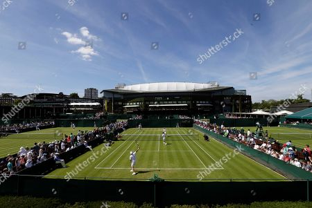 Spectators watch the men's doubles first round match Albert Ramos-Violas of Spain and Andreas Seppi of Italy against Jonathan Erlich of Israel and Philipp Petzschner of Germany at the All England Lawn Tennis Championships in Wimbledon, London