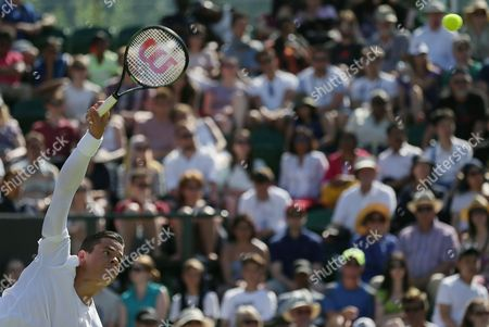 Milos Raonic of Canada serves to Daniel Gimeno-Traver of Spain during the men's singles first round match at the All England Lawn Tennis Championships in Wimbledon, London