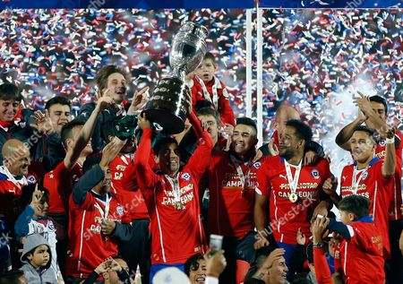 Chile's David Pizarro lifts the trophy after winning the Copa America final soccer match at the National Stadium in Santiago, Chile, . Chile defeated Argentina 4-1 in a penalty shoot out after the game ended in a 0-0 draw
