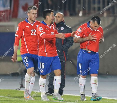 Gary Medel, Angelo Henriquez, David Pizarro Chile's Gary Medel, right, kisses the ball underneath his jersey after scoring against Bolivia followed by teammates Chile's Angelo Henriquez, left, and Chile's David Pizarro, center, during a Copa America Group A soccer match at El Nacional stadium in Santiago, Chile