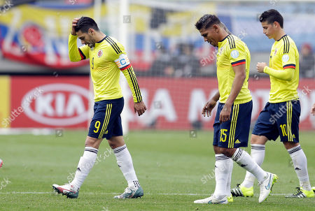 Stock Photo of Colombia's Radamel Falcao Garcia, Alexander Mejia and James Rodriguez, from left to right, leave the pitch at half time during a Copa America Group C soccer match against Peru at the Bicentenario German Becker stadium in Temuco, Chile