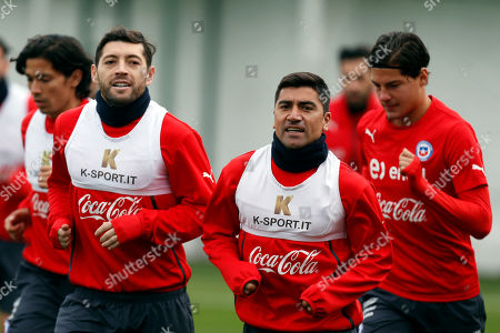 Jose Rojas, David Pizarro, Miiko Albornoz Chile's David Pizarro, right front, and teammates, Jose Rojas, from left, Jose Rojas and Miiko Albornoz, warm up at the start of their soccer training session, ahead of their upcoming Copa America match, in Santiago, Chile, . Pizarro, 35, will take part in his second Copa America, 19 years after his first. Chile will face Ecuador in the soccer tournament's inaugural match Thursday