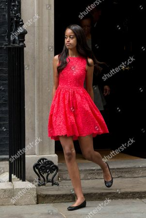 CORRECTS NAME TO SASHA, INSTEAD OF NATASHA - Malia, the daughter of U.S. first lady Michelle Obama, leaves after joining her mum and sister Sasha to visit British Prime Minister David Cameron and his wife Samantha at 10 Downing Street, in London, . Schoolgirls in east London greeted U.S. first lady Michelle Obama with song, interpretive dance and squeals of joy Tuesday as she traveled to the British capital to promote education for girls