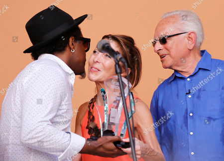 Cuban sculptor Alexandre Arrechea, left, gets his U.S.-based Farber Foundation award from the hands of Howard Farber, right, and his wife Patricia in Havana, Cuba, . Arrechea was named Cuban Artist of the Year by the foundation at a ceremony in Old Havana. The award comes with a $10.000 prize